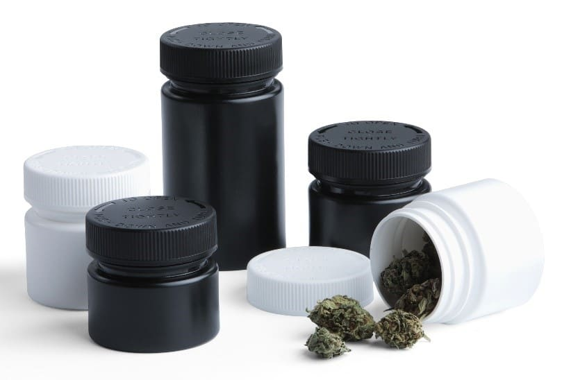 Black and white plastic bottles with cannabis product falling out